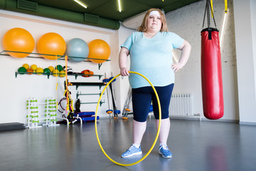 Full length portrait of  obese young woman posing with hula hoop  during weightloss training in gym, copy space