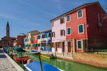 Houses and church on the canal with boats docked at Burano near Venice.