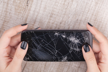 Smartphone with a broken screen in the girl's hand