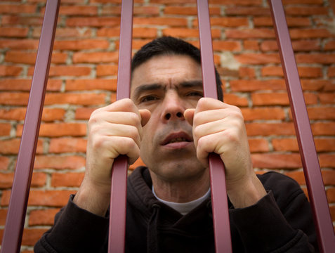 The prisoner behind the bars.Hold with hands on the grids