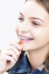 Dental Health Ideas and Concepts.Smiling Caucasian Female Teenager With Teeth Braces. Cleaning Brackets Using Bristle Brush.