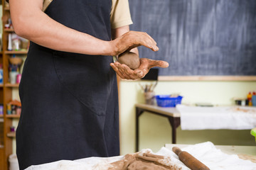 Concepts of Ceramist in Workshop. Working  Hands of Male Potter Professional Making a Clay Lump in Studio.