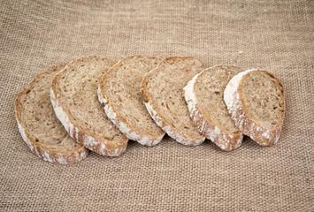Sliced brown bread on burlap.