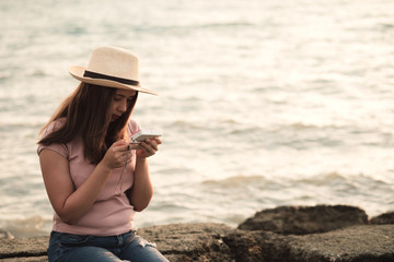 Young asian woman wear straw hat sitting on the rock checking her picture in digital camera at sea shore in evening sunset. Alone traveler traveling in summer holiday and vacation in tropical sea.