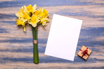 Workplace with a gift with a red ribbon, a piece of paper and a bouquet of daffodils on a blue wooden background. Flat lay design, top view.