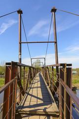 Old iron pedestrian bridge over the river Izhora.