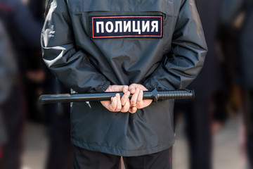 Russian policeman with police truncheon. Text in russian: Police