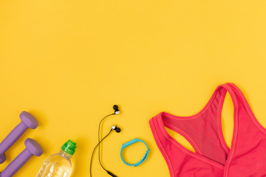 Woman's accessories for sport and bottle of water on yellow background. Flat lay, top view.