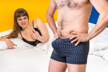 Woman in bed and man in underwear - potency concept
