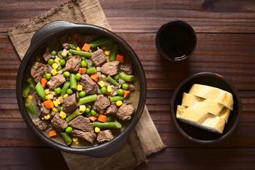 Eintopf aus Rindfleisch und buntem Gemüse (Erbsen, Karotten, Mais, Bohnen, Zwiebel), Rotwein und Brot an der Seite, fotografiert mit natürlichem Licht