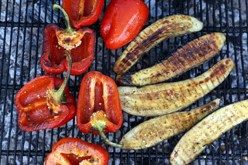 Close-up red pepper and slices of eggplant are grilled. Open fire kitchen. BBQ Restaurant. Red grilled pepper on bbq fireplace