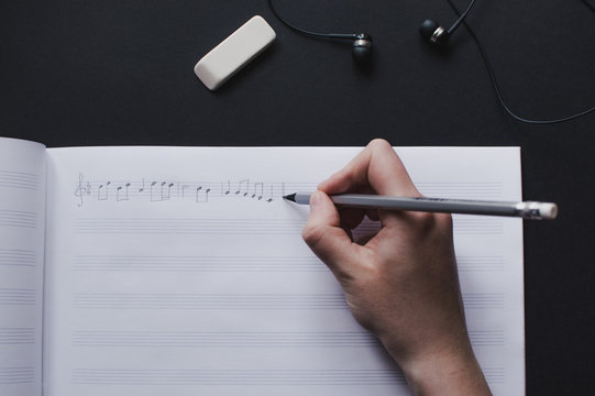 Top view of the female's hand writing music notes in the empty sheet music. The concept of the music creating, composing, note writing, music art.