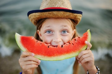 baby girl in the hat eagerly eats juicy watermelon on sea background
