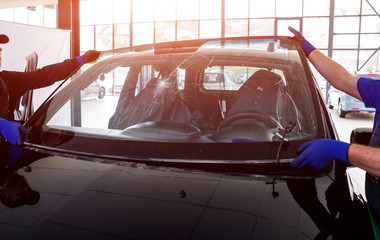 Automobile special workers remove old windscreen or windshield of a car in auto service station garage.