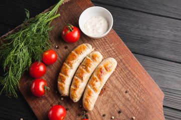 Grilled sausages grilled on a brown wooden board on a wooden background, six cherry tomatoes, greens, parsley dill, pepper, sauce. Place under the text and logo. Top view. Flat lay.