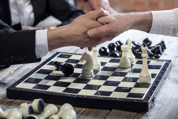 People shaking hands over chessboard