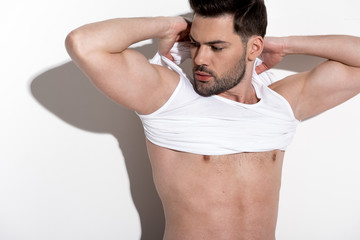 Young sexual man is taking off his shirt while standing against light background. He is looking aside thoughtfully while holding hands behind his head