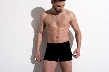 Youn shirtless healthy athletic man is standing against light background. He is posing wearing boxer briefs. Beauty concept