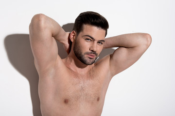 Perfect skin. Portrait of charming topless guy is standing against light background and demonstrating his smooth armpits. He is raising his arms up while looking at camera confidently