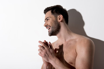 Happy day. Side view profile of positive bearded topless man is standing against light background and looking aside with smile. Copy space in the left side. Beauty concept