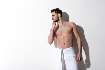 What is this. Young charming guy is standing with towel on hips and looking aside with concentration. He is touching his chin while posing against light background. Copy space in the left side