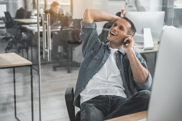 Portrait of happy male telling by phone during labor. He sitting at desk