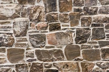 Grunge uneven mosaic stone wall background.