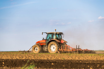 Wall Mural - Tractor cultivating field at spring