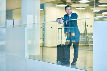 Full length portrait pf modern Asian man wearing business suit standing at window in airport waiting for flight with baggage, copy space