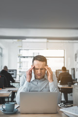 Portrait of sad businessman feeling pain in head while using laptop. Unhappy worker in office concept