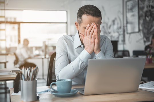Depressed employer closing face while sitting at desk during job. Unhappy manager concept