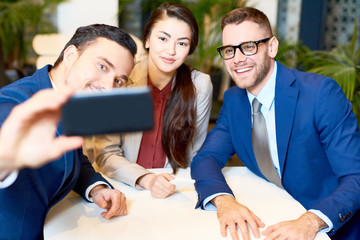 Portrait of three young business people taking group selfie via smartphone while sitting at cafe table during coffee break