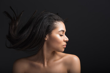 Profile of serene girl with closed eyes. She is waving her hairdo. Isolated on black background
