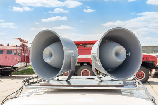 Pair of big retro loudspeakers on car roof. Fire trucks on background. Urgent or emergency announcement concept