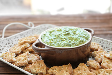 Casserole with tasty spinach sauce and crackers on tray