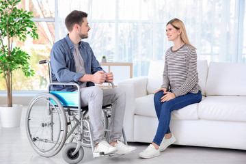 Young woman talking to man in wheelchair indoors