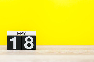 May 18th. Day 18 of may month, calendar on yellow background. Spring time, empty space for text