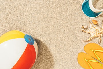 top view of arrangement of colorful beach ball, flip flops and cap on sand