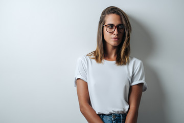 Handsome woman in white blank t-shirt wearing glasses, empty wall, horizontal studio portrait Wall mural