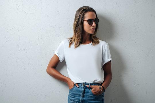 Stylish woman in white blank t-shirt wearing glasses, grunge wall, horizontal studio portrait