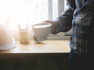 Man holding a cup of coffee by the window.
