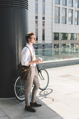 stylish young man with coffee to go and vintage bicycle on rooftop of business building