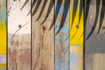 Colorful wooden surface with palm leaf shadow. Painted timber texture. Natural boho background