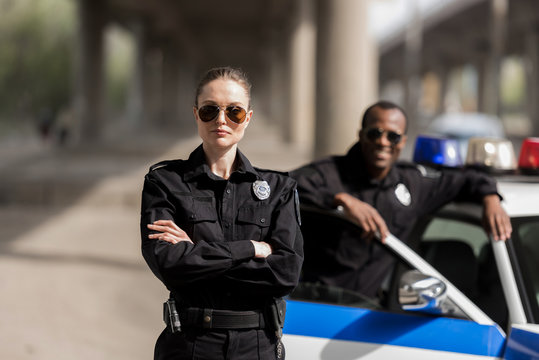young serious policewoman standing with crossed arms while her partner standing near car and smiling blurred on background