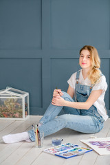art creativity concept. drawing hobby. artful person leisure. painter lifestyle. young beautiful girl sitting on the floor surrounded by her artwork