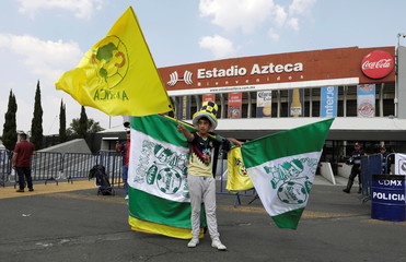 A vendor waves domestic football team flags with logos of Club America and Club Santos Laguna for sale outside the Azteca stadium of Mexican First Division in Mexico City