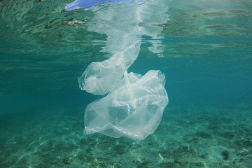 Plastic pollution in ocean. Plastic bags, bottles and straws pollute sea