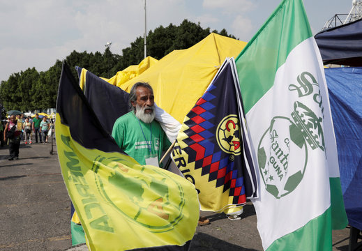 A vendor carries domestic football teams' flags with logos of Club Santos Laguna and Club America for sale outside the Azteca stadium of Mexican First Division in Mexico City