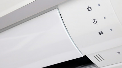 The air conditioner with indicators,, close up view. The cooling device is mounted on the room wall.