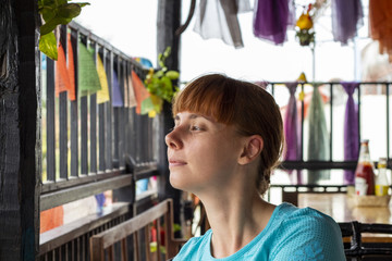 Relaxed woman in cambodian cafe. Outdoor cafe with balcony and asian style interior.
